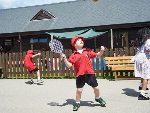 Children playing tennis in playground